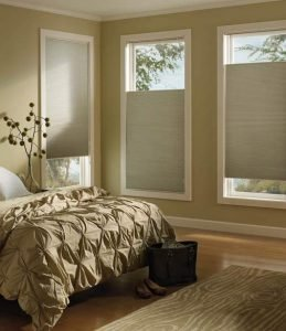 A bedroom with cellular window shades at different levels, with a custom bed and rug in it.