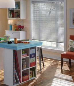 A craft room with chairs, tables, and a window with metal window blinds.