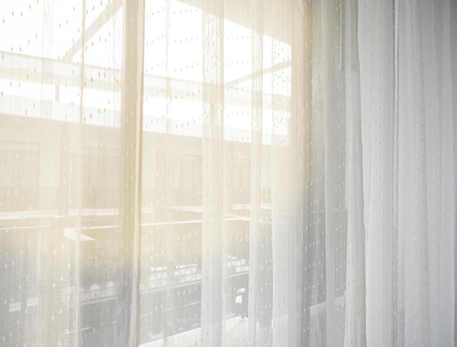 A bedroom with a see-through white curtain