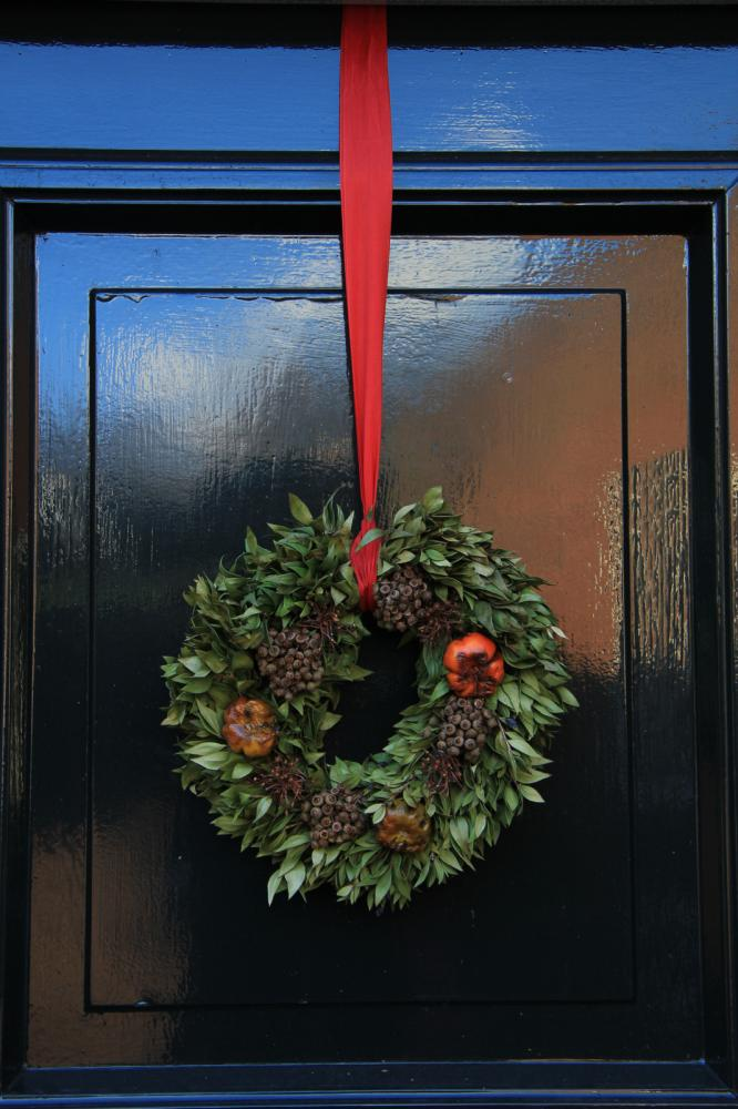 A black door with a Christmas wreath tied with a red ribbon
