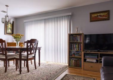 A living room with blinds, dining table, and a TV console