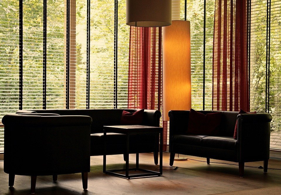 A lounge with large windows with blinds