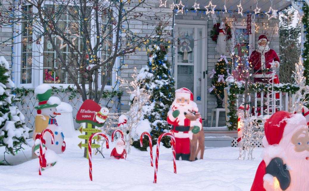 A front porch of the house decorated with candy canes and Santa