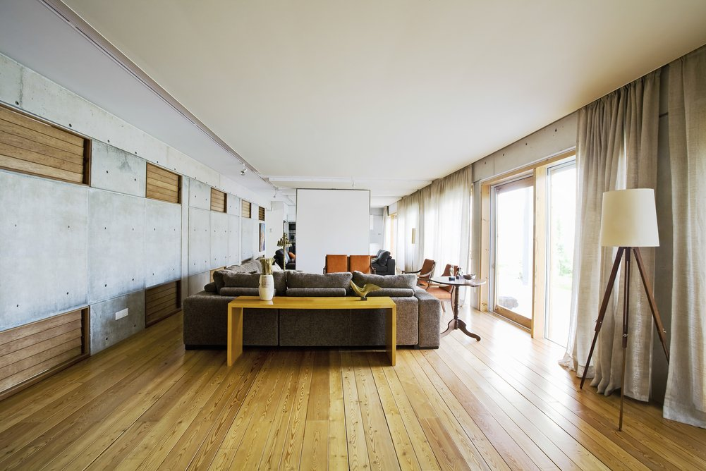 A spacious minimal living room with ceiling mounted curtains