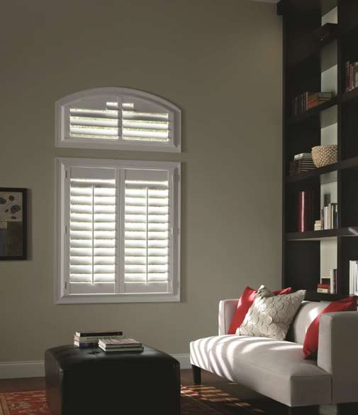A living room with a window installed with vinyl shutters