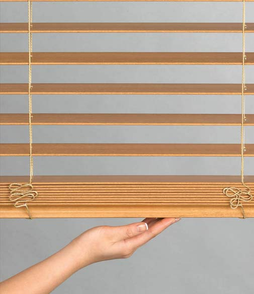 A person is holding wooden window blinds