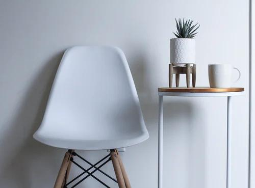 a white chair and a plant